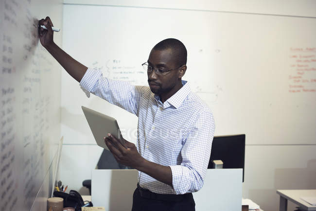 Бізнесмен, написи на дошці в офісі — стокове фото