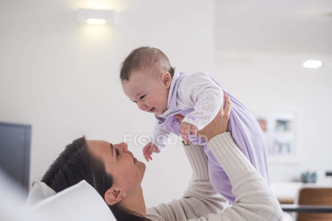 Mother holding up baby girl at home — Stock Photo