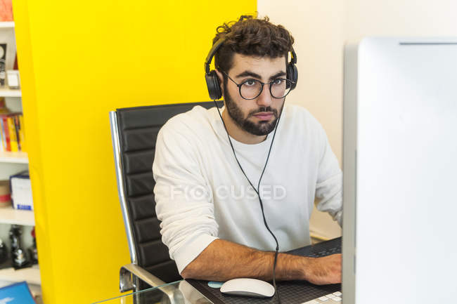 Young man working with computer in office — Stock Photo