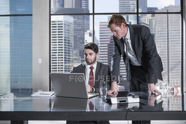 Businessman and woman in meeting discussing in office, using laptop — Stock Photo