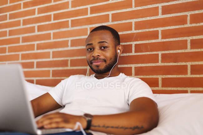 Портрет молодої людини з навушників на ліжко, використовуючи ноутбук — стокове фото