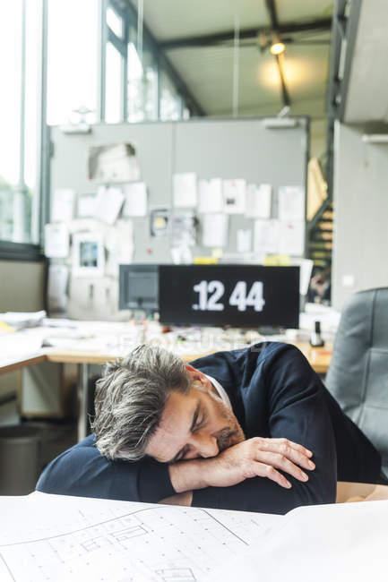 Excesso de trabalho arquiteto dormindo na mesa no escritório — Fotografia de Stock