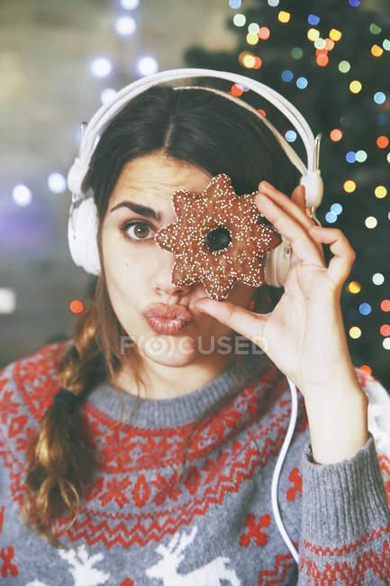 Mujer con auriculares mirando a través de una galleta de Navidad - foto de stock