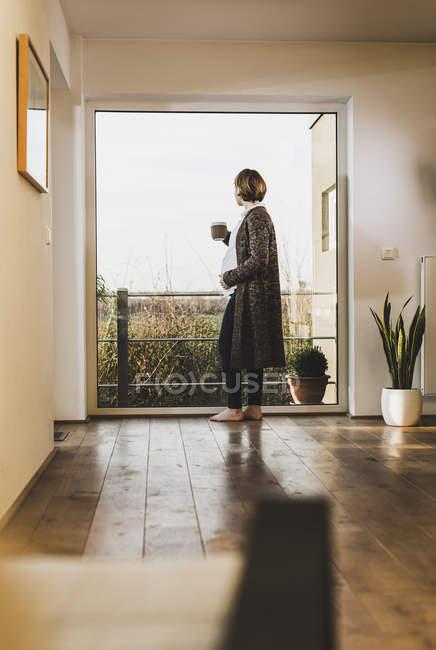 Беременная женщина стоит у окна, держа в руках кружку. — стоковое фото