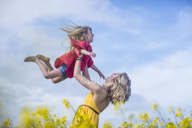 Mère et petite fille s'amusent ensemble dans un champ de viol — Photo de stock