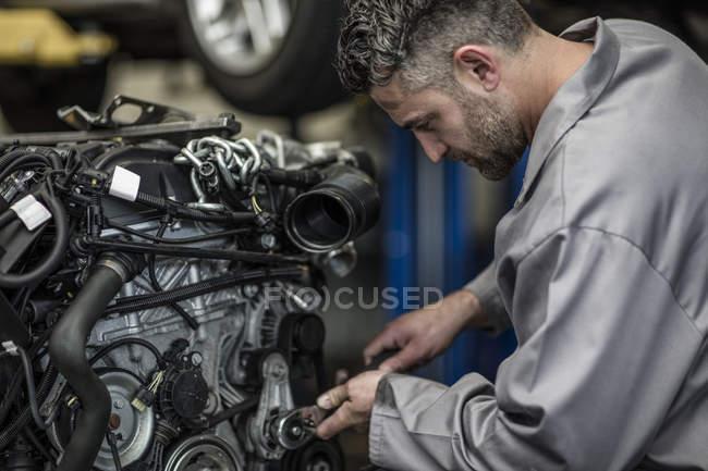 Car mechanic in a workshop repairing engine — Stock Photo