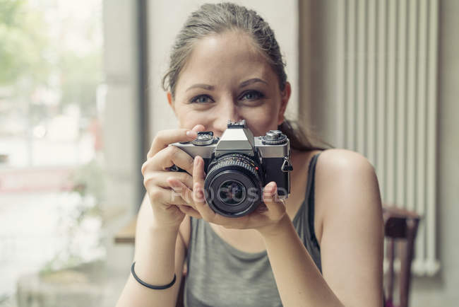 Portrait of smiling young woman holding a camera — Stock Photo