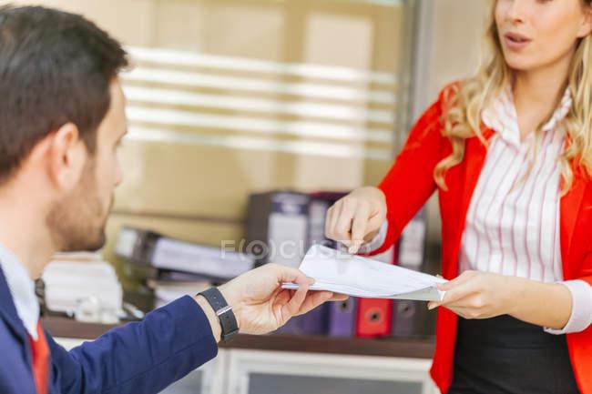 Sekretärin Übergabe Dokument zum Geschäftsmann im Büro — Stockfoto