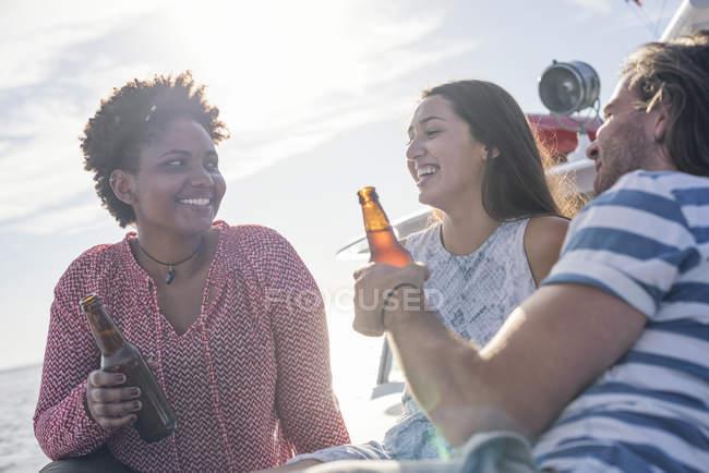 Счастливые друзья во время прогулки на лодке пьют пиво — стоковое фото