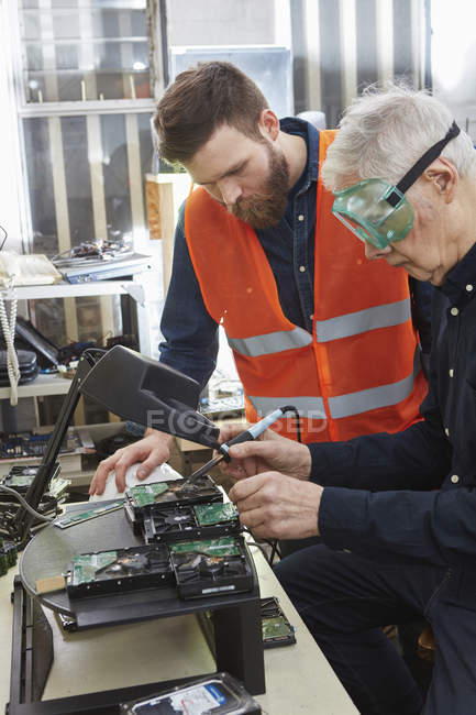 Workers in computer recycling plant dismantling hard disk — Stock Photo