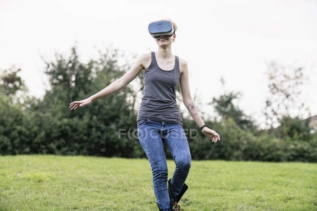 Smiling young woman using Virtual Reality Glasses outdoors — Stock Photo