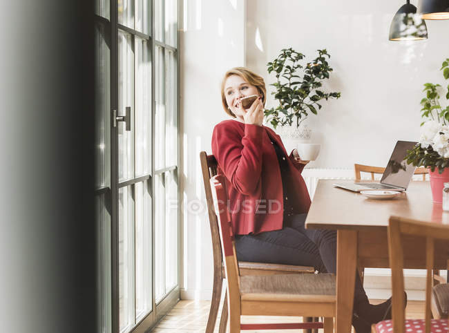 Smiling young woman using cell phone in a cafe — Stock Photo