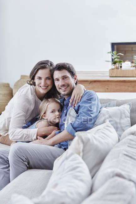 Сім'я з донька розслаблюючий на канапі в домашніх умовах — стокове фото