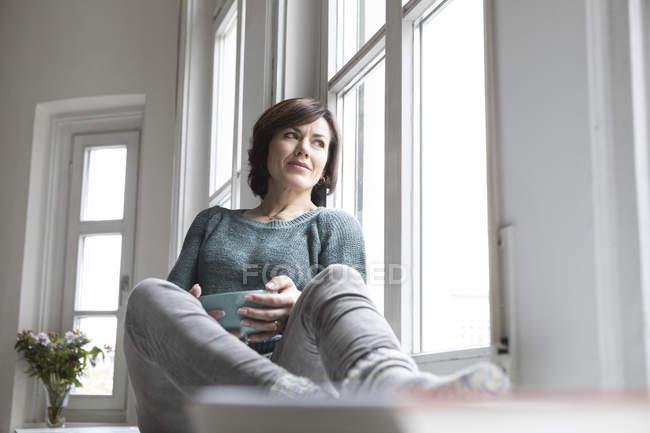 Mulher olhando pela janela enquanto sentada no peitoril da janela em casa — Fotografia de Stock