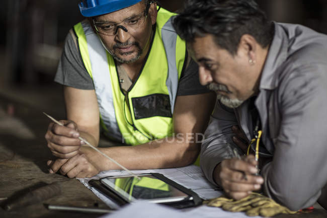 Engineers discussing construction plans on digital tablet — Stock Photo