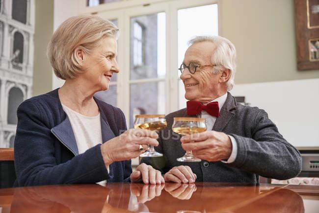 Smiling senior couple clinking champagne glasses — Stock Photo