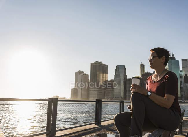 Жінка з каву йти сидять на лавці і дивлячись на перегляд — стокове фото