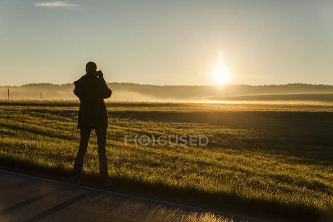 Woman photographing sunrise standing at summer field — Stock Photo