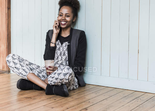 Smiling young woman sitting on floor and talking on cell phone — Stock Photo
