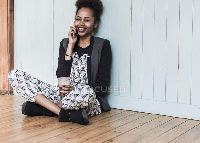 Lächelnde junge Frau sitzt auf dem Boden und telefoniert — Stockfoto
