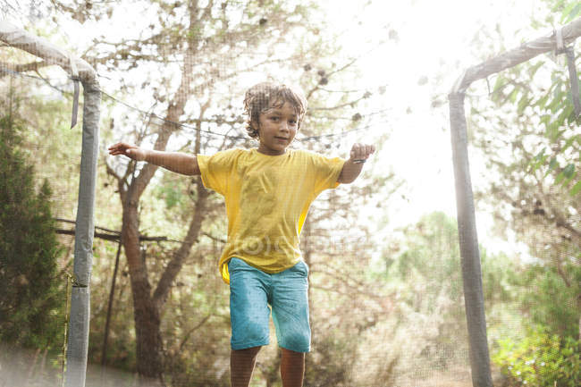 Little boy jumping on trampoline in nature — Stock Photo