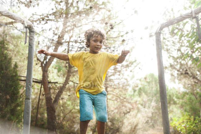 Petit garçon sauter sur le trampoline dans la nature — Photo de stock