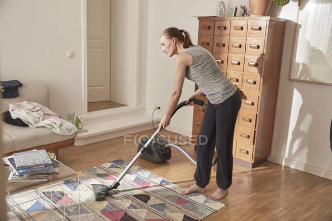 Vuoto di donna pulizia tappeto a casa — Foto stock