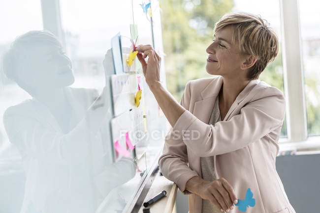 Businesswoman putting notes on whiteboard in office — Stock Photo
