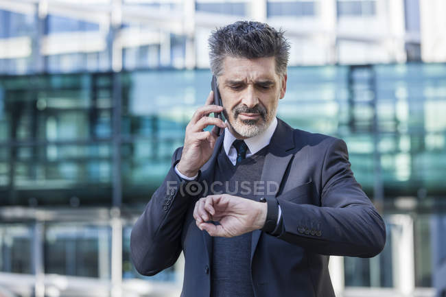 Businessman talking on cell phone and checking the time in front of office building — Stock Photo