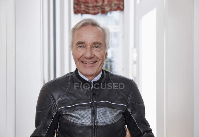 Portrait of smiling senior man in motorcycle suit — Stock Photo