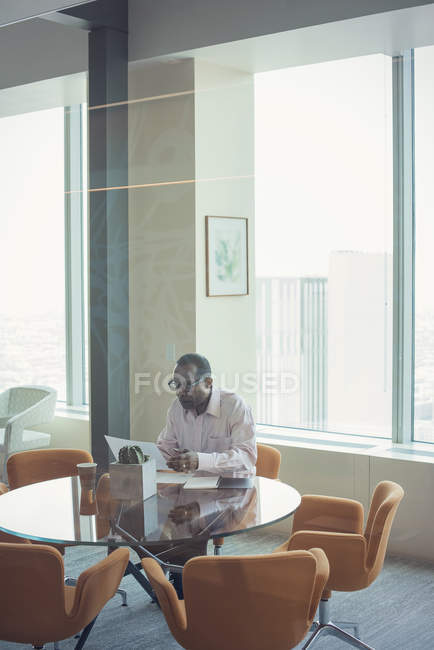 Businessman reading documents alone in office — Stock Photo