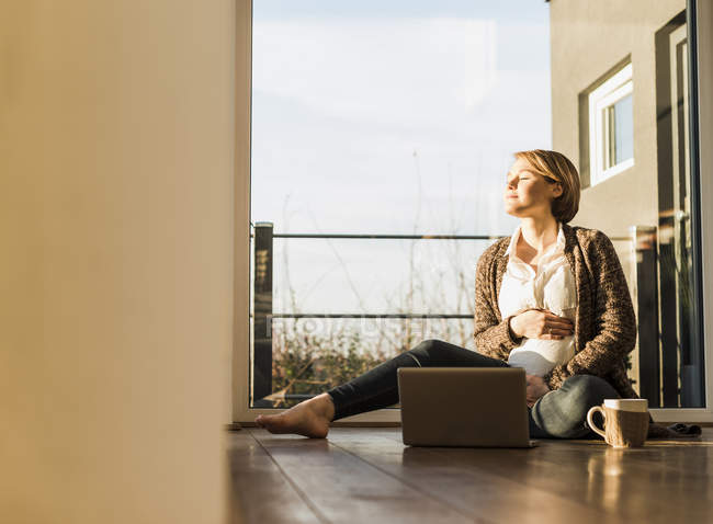 Pregnant woman sitting on floor with laptop enjoying the sunshine — Stock Photo
