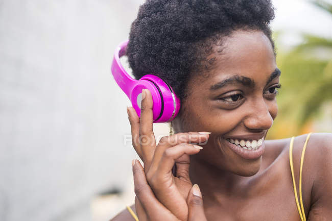 Young attractive african american girl listening music in headphones — Stock Photo