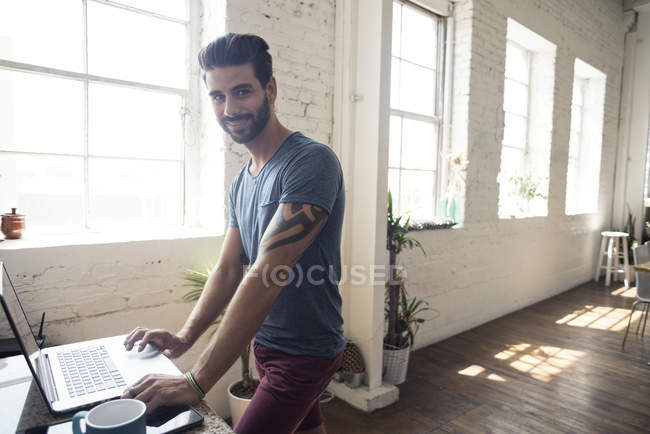 Jovem sorridente usando laptop em um loft — Fotografia de Stock