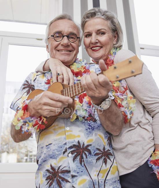 Glückliches Seniorenpaar mit Mann im hawaiianischen Hemd, der Ukulele spielt — Stockfoto