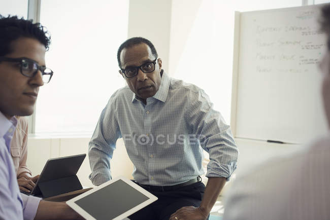 Business people with digital tablet sitting office, discussing — Stock Photo