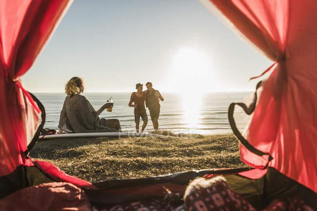Three friends camping at seaside at sunset — Stock Photo