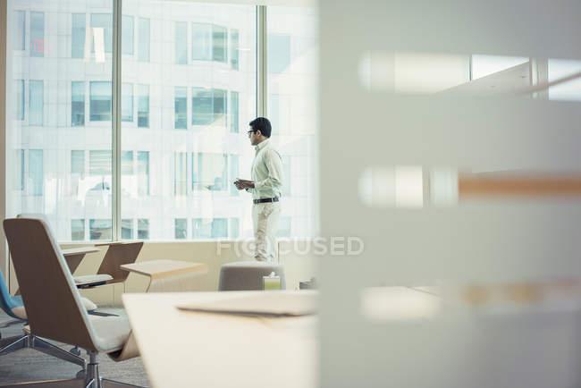 Впевнено бізнесмен стоять біля вікна в офісі — стокове фото