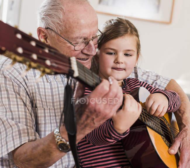 Abuelo y nieta tocando juntos la guitarra - foto de stock