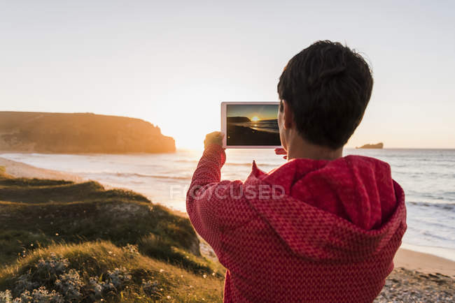 Woman taking picture with tablet at the coast at sunset — Stock Photo