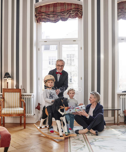 Abuelos y nietos con caballo y regalo - foto de stock