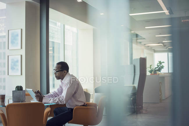Businessman working alone in office, using digital tablet — Stock Photo