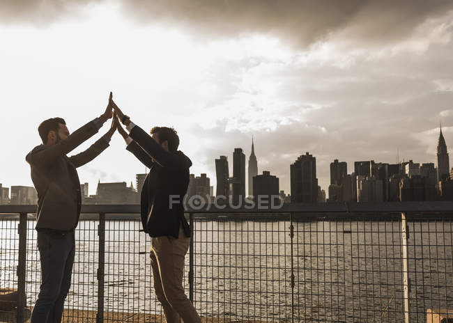Two businessmen giving high five at East River, New York City, USA — Stock Photo