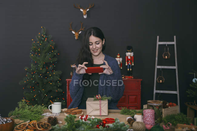 Smiling young woman photographing decorated Christmas gift with smartphone — Stock Photo