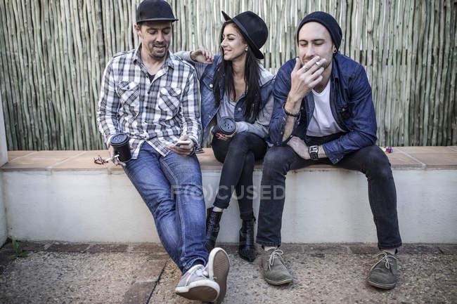 Молодая женщина и двое мужчин сидят на улице — стоковое фото