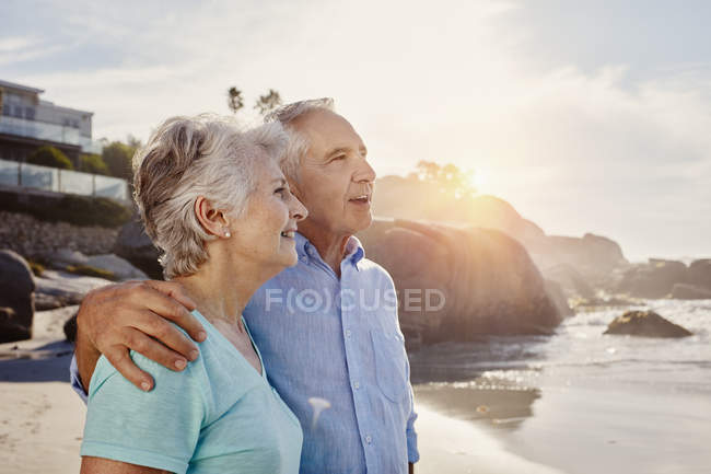 Senior couple looking at sunset on the beach — Stock Photo