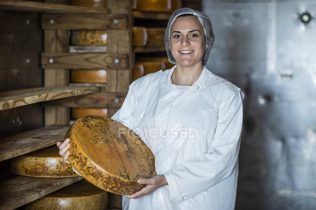Cheese factory worker proudly holding loaf of cheese — Stock Photo