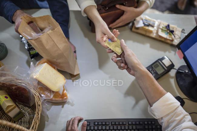 Cliente paga con tarjeta de crédito en una tienda de la granja - foto de stock