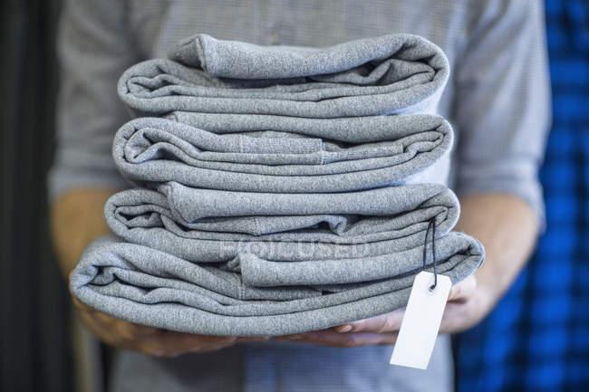 Ritagliate l'immagine dell'uomo che tiene la pila di vestiti piegati — Foto stock