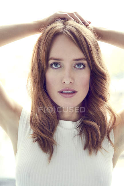 Portrait of redheaded woman with hands behind head — Stock Photo